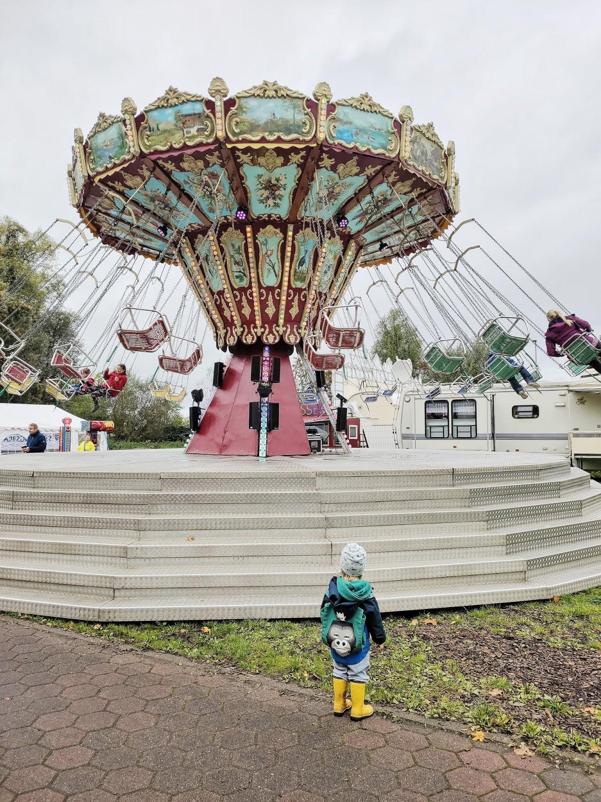 Kind steht vor einem Kettenkarussell