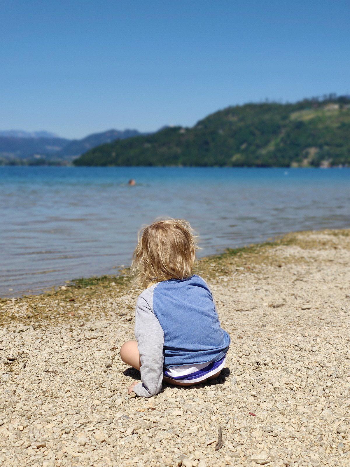 Kleines Kind sitzt am Strand